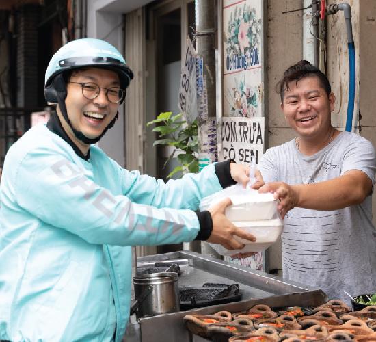 Đối tác Tài xế BAEMIN nhận đồ ăn từ Đối tác Nhà hàng để giao đến tay của Khác hàng
